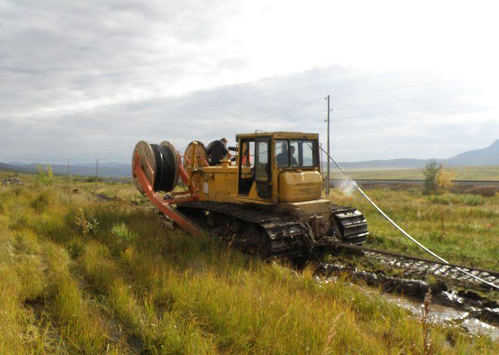 Третий трактор-тягач помогает двигаться укладчику и несет резерв кабеля