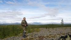 Перминов на вершине левого борта ручья Прохладный. Вдали главные хребты Полярного Урала