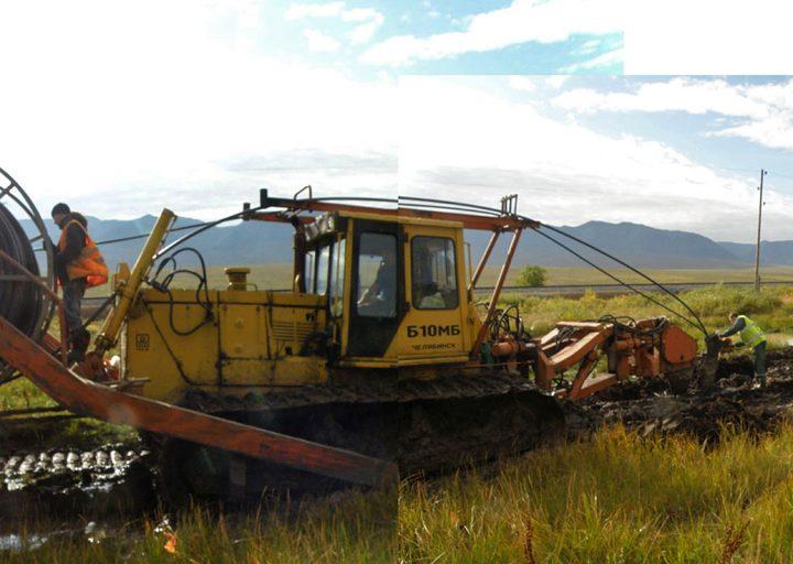 Четвертый трактор заправляет кабель в прорезанную траншею